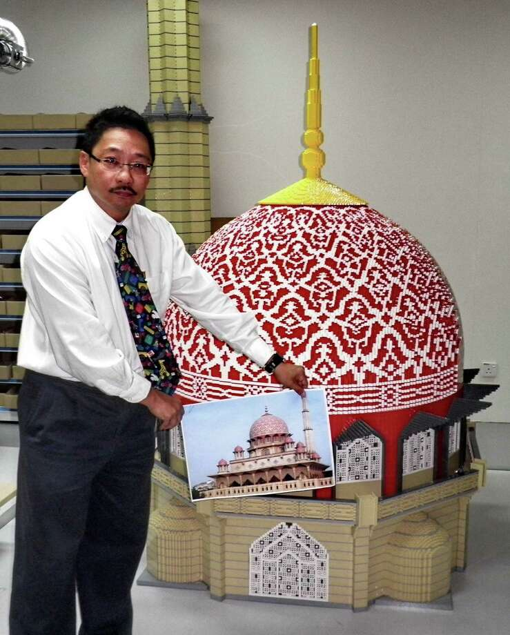 Zainal Ashikin Muhammad, chief executive of IDR Resorts, which built Asia's first Legoland, displays a photo of a famous Malaysian mosque in front of a Lego replica on February 22, 2011 in Johor Bahru. Photo: MARTIN ABUGGAO, AFP/Getty Images / 2011 AFP