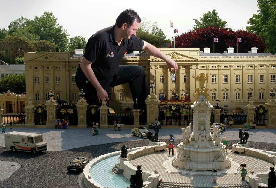 Model maker Giorgio Pastero places a Lego Queen Elizabeth II into a model of Buckingham Palace at Legoland, Windsor on May 24, 2012, before the Queen's Diamond Jubilee. Photo: ADRIAN DENNIS, AFP/Getty Images / 2012 AFP