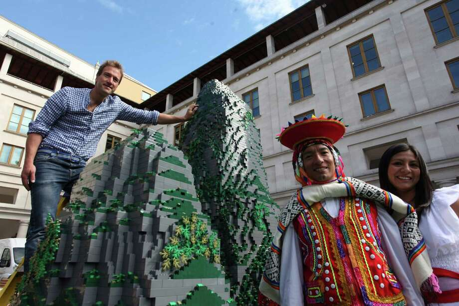 Ben Fogle poses for a picture with a couple of Peruvians in traditional dress near a Lego model of Machu Pichu at Convent Garden on June 26, 2012 in London, England. Photo: LatinContent/Getty Images