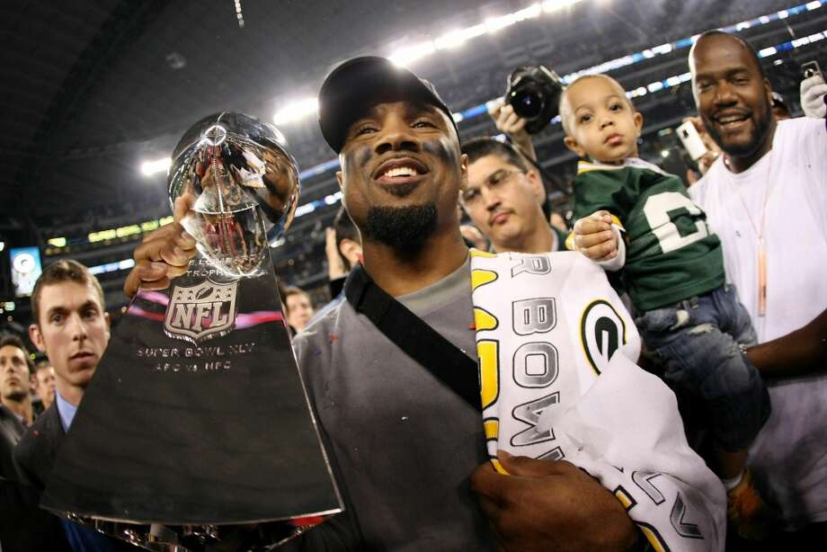 Charles Woodson of the Green Bay Packers, who was injured during the game, celebrates with the Vince Lombardi Trophy after they defeated the Pittsburgh Steelers 31 to 25 in Super Bowl XLV.