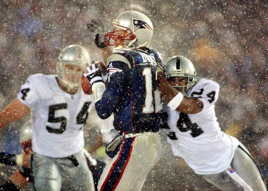 New England Patriots  quarterback Tom Brady (C) takes a hit from Charles Woodson (R) of the Oakland Raiders on a pass attempt in the last two minutes of the game in their AFC playoff 19 January 2002 in Foxboro, Massachusetts.