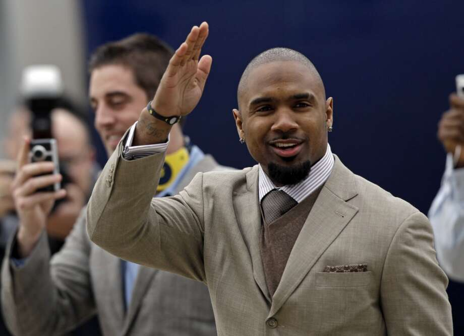 Green Bay Packers' Charles Woodson waves as they arrive at Dallas/Fort Worth International Airport for Super Bowl XLV.