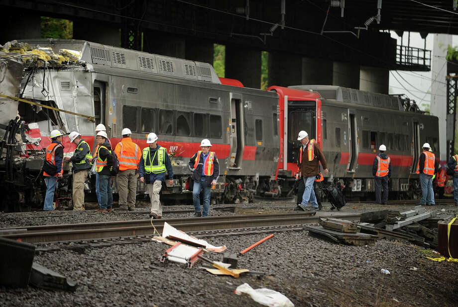 Metro North workers at the site of Friday's train derailment in Bridgeport. Conn. on Sunday, May 19, 2013. Derailed train cars were being hoisted back on to the tracks and pulled away from the scene. Federal investigators have highlighted two pieces of rail they say were found broken at a joint bar at the accident scene in the area of the crash which injured 76 people. Photo: Brian A. Pounds / Connecticut Post