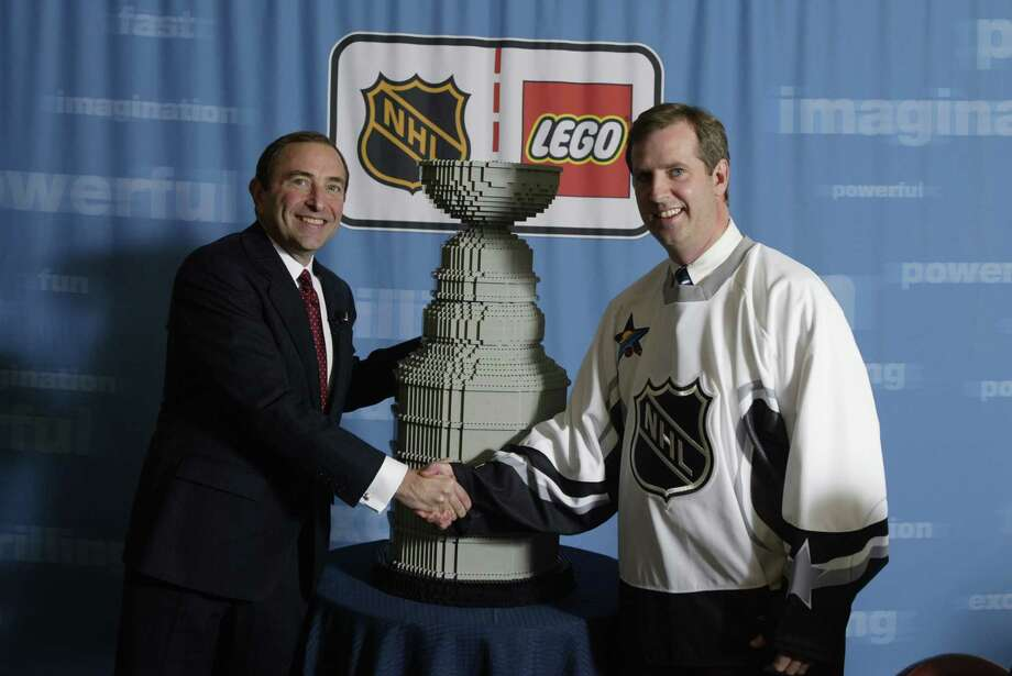 NHL Commisioner Gary Bettman (left) and Lego President Andrew Black shake hands in front of a Lego Stanley Cup after announcing a multi-year global alliance on November 19, 2002 in New York. Photo: Al Bello, Getty Images/NHLI / 2002 Getty Images