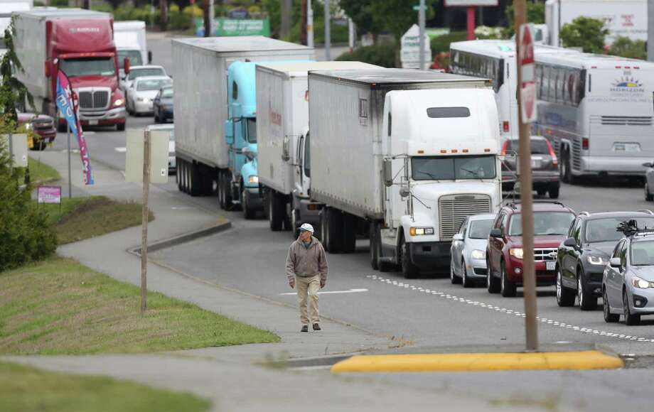 A man walks along South Burlington Boulevard, and backed up freeway traffic, the day after the Interstate 5 bridge over the Skagit River between Mount. Vernon and Burlington, Wash.,  collapsed. Three people were rescued from the water. Two cars and one travel 