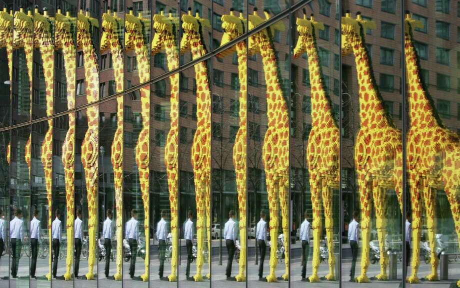 A man walks past a giant giraffe made of Lego bricks and reflected in a glass facade in Berlin on March 29, 2007. Photo: JOHN MACDOUGALL, AFP/Getty Images / 2007 AFP