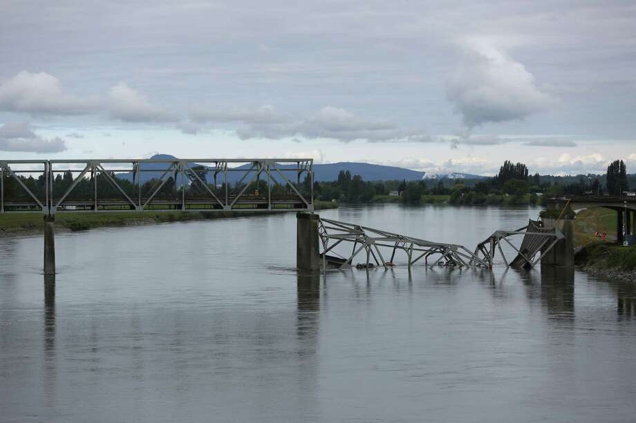 The crumpled I-5 bridge is shown the day after the bridge over the Skagit River between Mount Vernon and Burlington, Wash., collapsed. Three people were rescued from the water. Two cars and one travel 