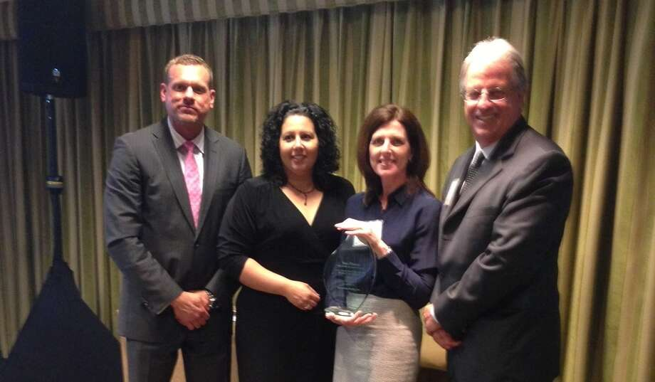 Mary Piper (second from right), Bernstein Realty's director of relocation and operations, accepts the award. She is shown with representatives from TheMIGroup, (from left): Dwayne Waldrop, vice president, supply chain management; Laurissa Norwick, vice president, domestic consulting and process management; and Andy Neall, vice president, client relations.