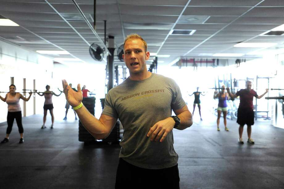 "Drew Bignall will be vying for the title of ""Fittest Man on Earth"" this weekend. He owns Mission CrossFit Gym, where he works with patrons on Thursday, May 23, 2013. Photo: Billy Calzada, San Antonio Express-News / San Antonio Express-News"