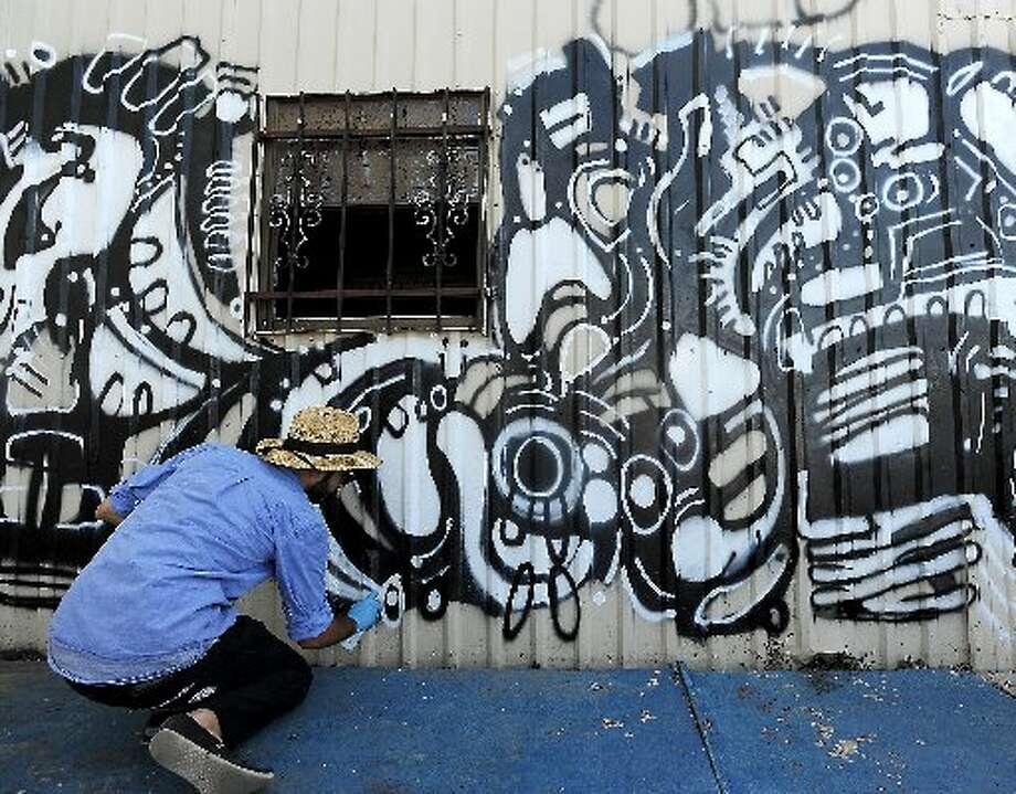 Carlo Busceme IV creates a mural for the outdoor seating area at Taco la Bamba. cat5 file photo