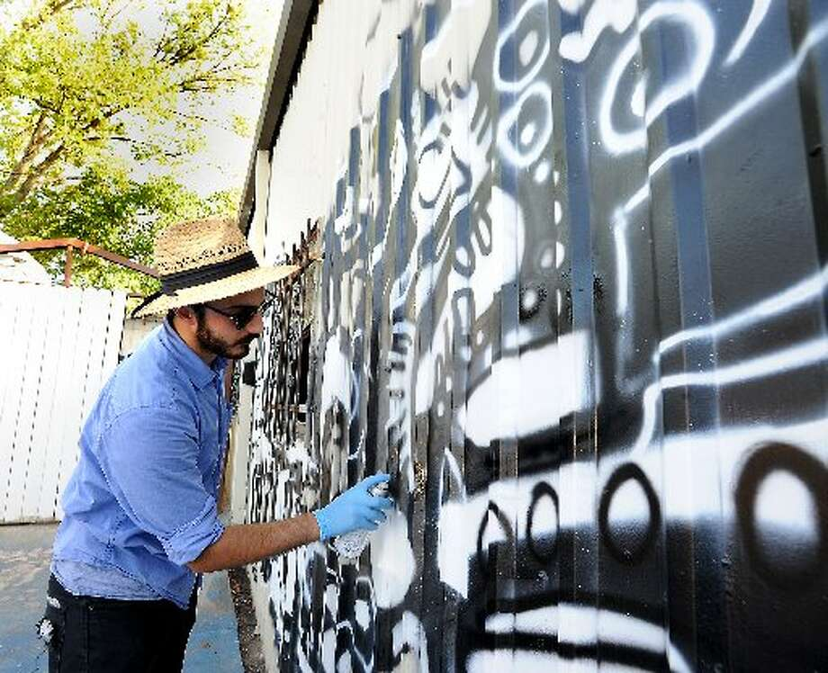 Carlo Busceme IV creates a mural for the outdoor seating area at Taco la Bamba. cat5 file photo