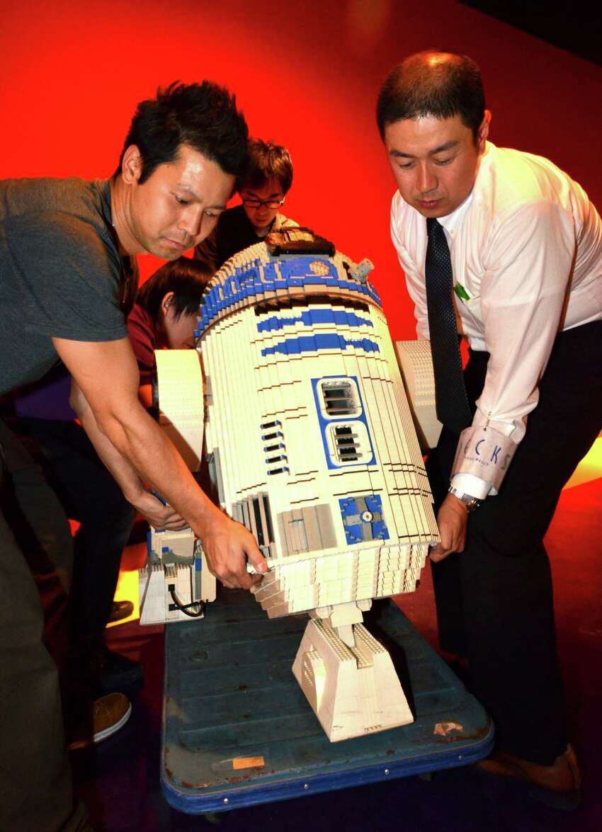 Employees of Lego Japan carry Lego R2-D2 on November 5, 2012 at the Legoland Discovery Center Tokyo.