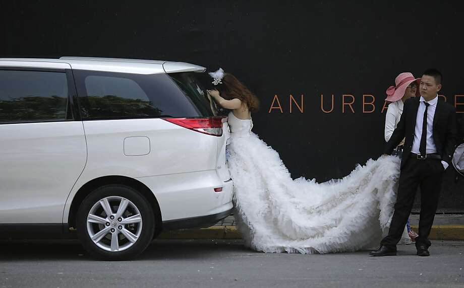 Welcome to the rest of your life, son:A restless groom dutifully holds the train of his new bride as she looks for something in the back of an SUV in Shanghai. Photo: Eugene Hoshiko, Associated Press