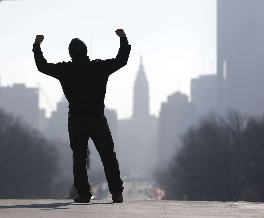 Getting strong now, won't be long now, getting strong now:A tourist imitates the Rocky Balboa statue (not shown) on the steps of the Philadelphia Museum of Art. Photo: Matt Rourke, Associated Press