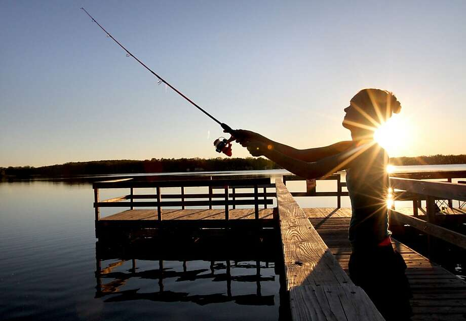 Casting call:Amanda Jacobs tries to squeeze in a little fishing before the sun sets on Whipple Lake in Baxter, Minn. Photo: Kelly Humphrey, Associated Press