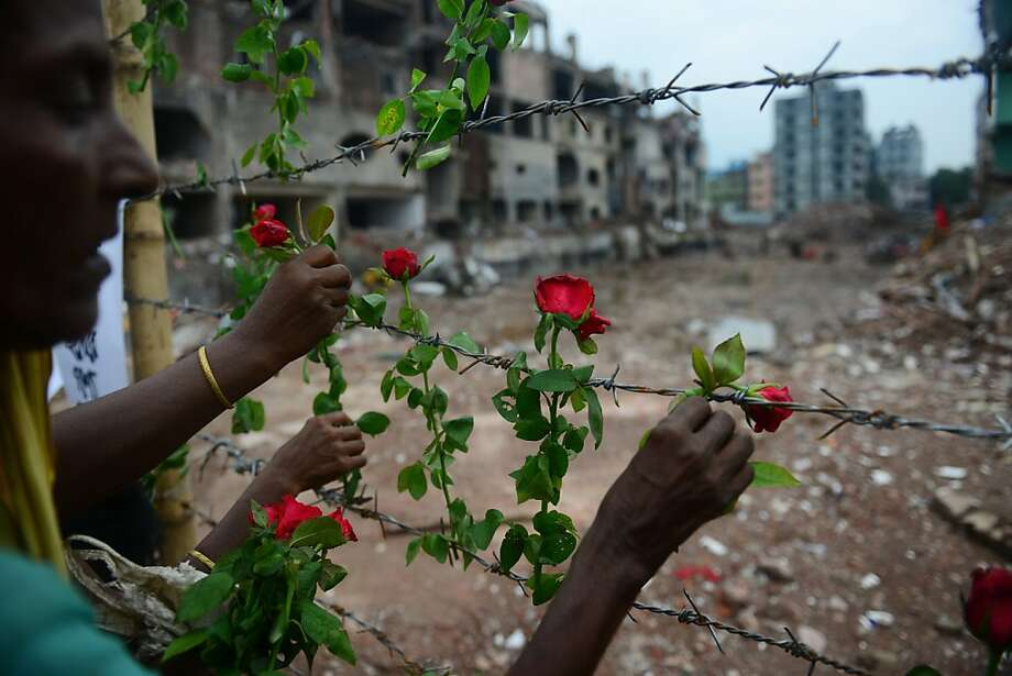 A Bangladeshi family member of a missing garment worker places roses on the barbed wire fence as she pays tribute to the victims at the site of the April 2013 nine-storey building collapse in Savar, on the outskirts of Dhaka on May 24, 2013.   Some 290 unidentified bodies were buried after DNA samples were collected to match those of relatives as the Bangladeshi army wrapped up its search May 14, 2013 for bodies at the site of the building collapse.   Industrial disasters since November have killed at least 1,250 workers, highlighting the appalling safety problems in the plants where three million workers toil for a basic monthly wages of USD 40, among the world's lowest.  AFP PHOTO/ Munir uz ZAMANMUNIR UZ ZAMAN/AFP/Getty Images Photo: Munir Uz Zaman, AFP/Getty Images
