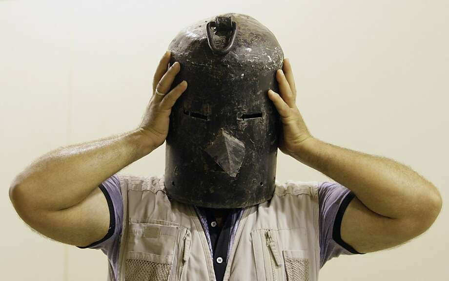 One size fits all: At the Shaheed Monument in Baghdad, an Iraqi tries on a metal helmet used for torturing Saddam Hussein's victims during the ousted leader's regime. Photo: Khalid Mohammed, Associated Press