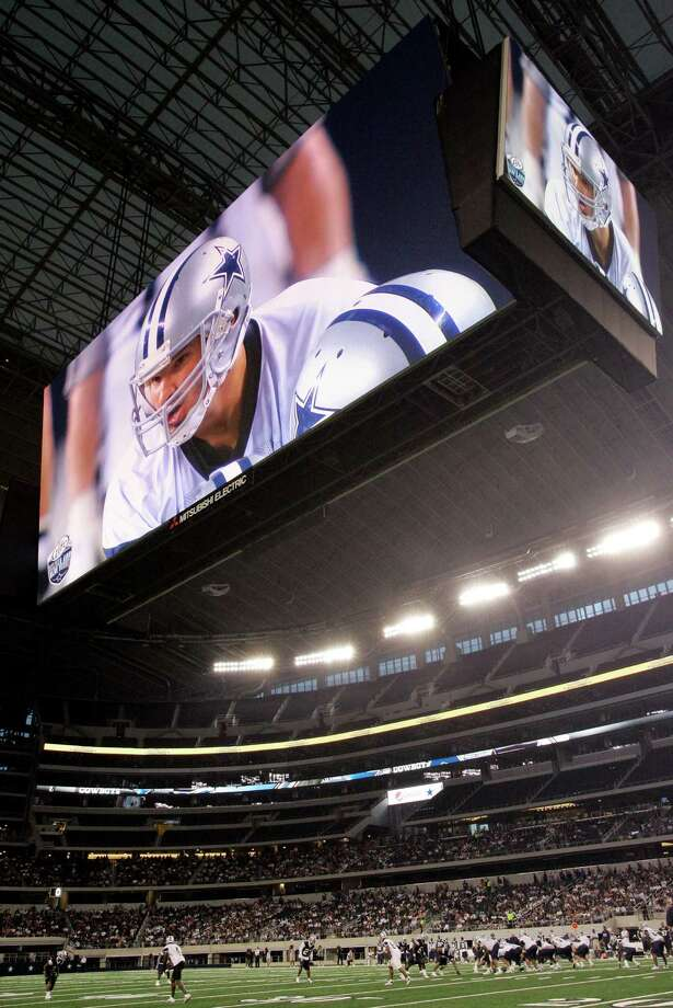 Quarterback Tony Romo projects a giant image in the video screen above Cowboys Stadium, but a reader expects little things from the Dallas Cowboys this year —  and for years to come.  Photo: Tony Gutierrez, Associated Press / AP