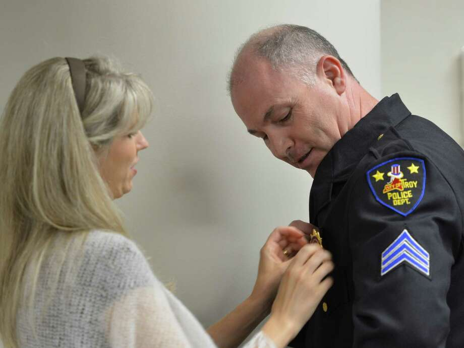 Thomas Bevevino, right,  is assisted by wife Debbie in putting his new shield on after being promoted to captain of the Troy Police Department May 24, 2013 in Troy, N.Y.    (Skip Dickstein/Times Union) Photo: SKIP DICKSTEIN / 00022572A