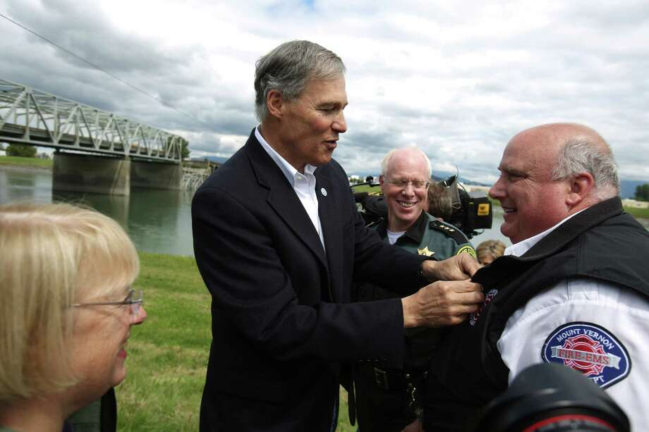 Governor Jay Inslee recognizes Mount Vernon battalion chief Mike Voss, who was incident commander as the Interstate 5 bridge over the Skagit River between Mt. Vernon and Burlington collapsed into the river. Three people were rescued after two cars and a travel trailer fell into the cold water. Photo: JOSHUA TRUJILLO, SEATTLEPI.COM / SEATTLEPI.COM