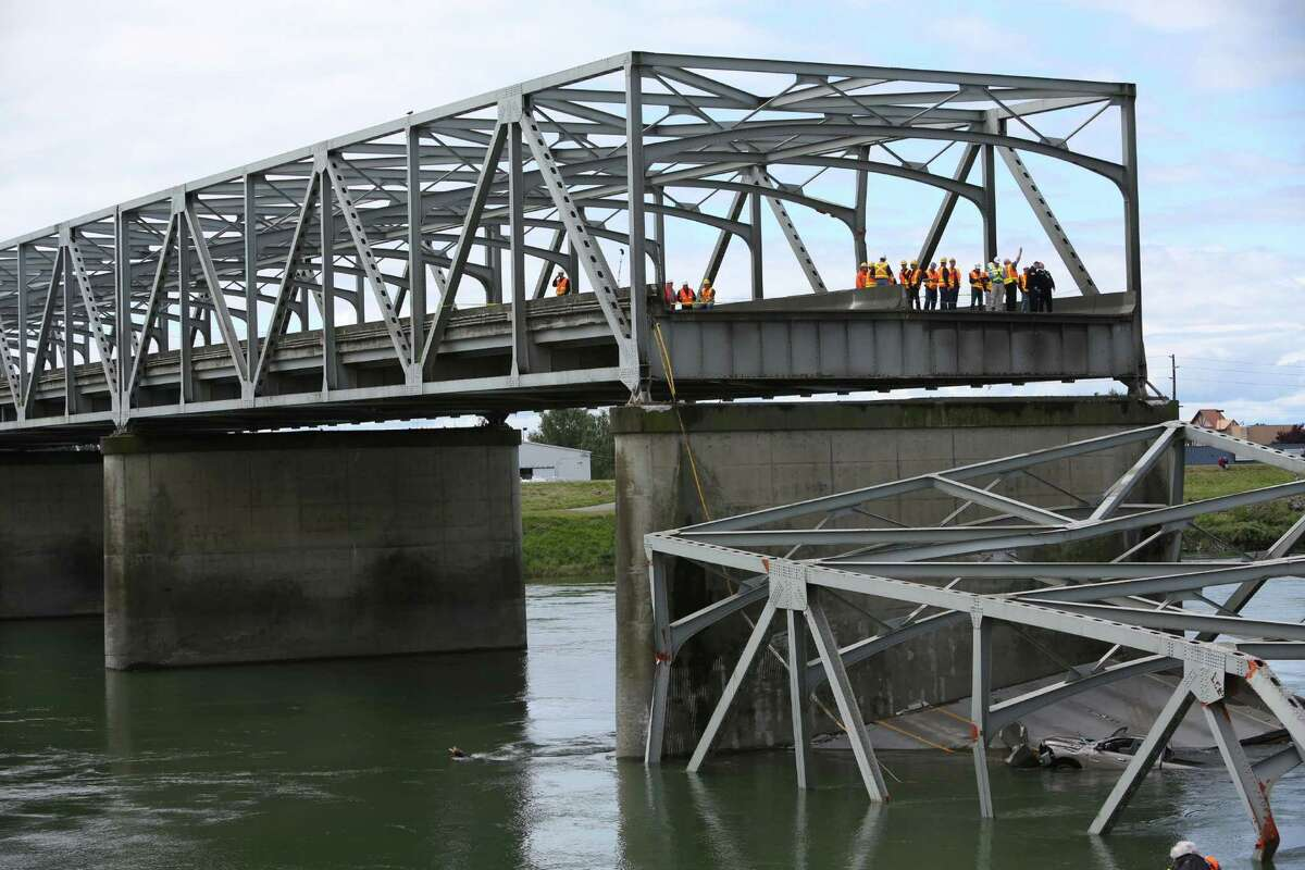 Inspectors look over the scene the day after the Interstate 5 bridge over the Skagit River between Mt. Vernon and Burlington collapsed into the river. Three people were rescued after two cars and a travel trailer fell into the cold water. There were no known fatalities.