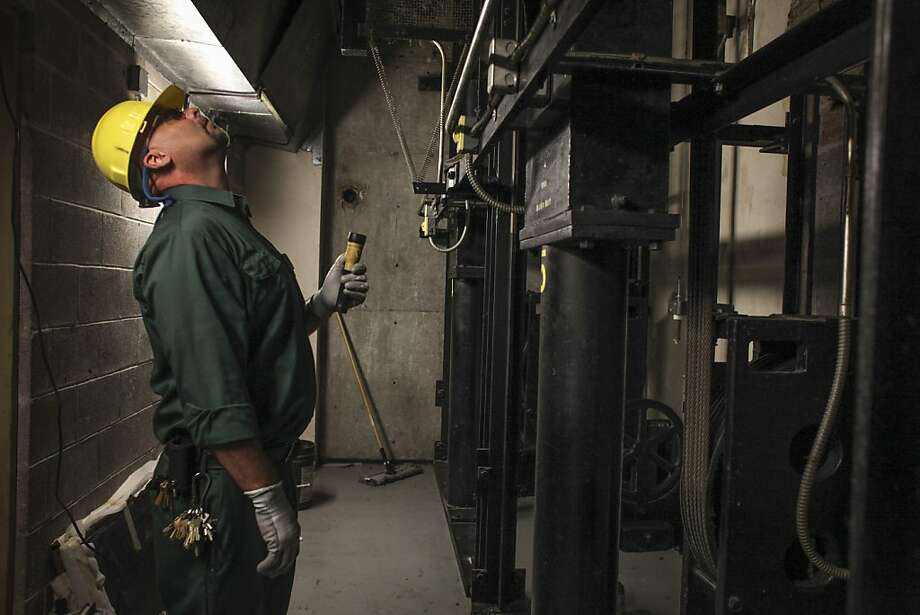 Randy Davenport, an adjustor for the Otis Elevator Co., looks up an elevator shaft from the elevator pit during a routine maintenance check at the 44 Montgomery St. building in S.F. Photo: Sam Wolson, Special To The Chronicle