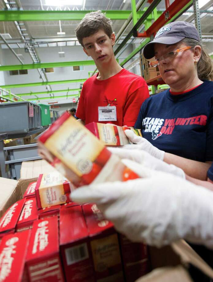 Clear Lake High School sophomore Constantine Tzouanas helps Dana Arp sort through donated food during a volunteer shift at the Houston Food Bank. Photo: J. Patric Schneider, Freelance / © 2013 Houston Chronicle