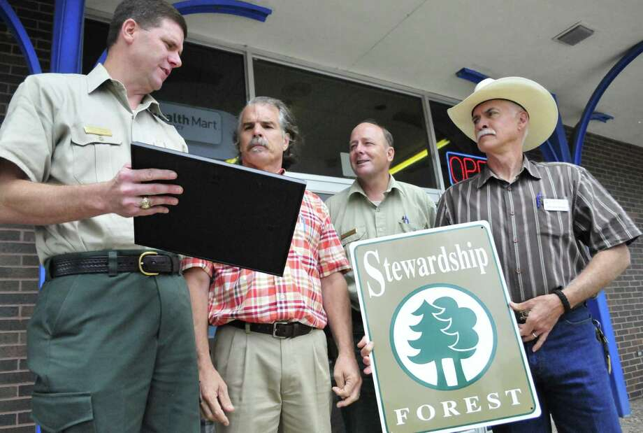 Kountze business owner Ken Bailey received a certification recognizing his commitment to a land stewardship ethic that focuses on timber management, fish and wildlife habitat, water quality, soil productivity, aesthetics and recreation. The award is for Bailey s foresight to establish a valuable legacy for future generations. It was presented by Dan Wilson, USDA/NRCS District Conservationist, Joel Hambright, Texas A&M Forest Service Regional Forester, and John Matel, Olive District Forester. Photo: Cassie Smith