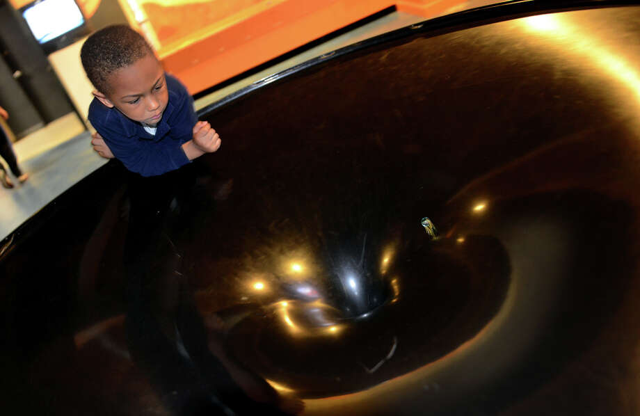 Matthew Jackson, 3, of Bridgeport, watches as a mable he released spins around and around inside a gravity well exhibit at the Discovery Museum in Bridgeport, Conn. on Friday May 24, 2013. The gravity well simulates the gravitational field surrounding objects orbiting in space. Jackson is home schooled by his mother Sharon Bunting and the museum was a field trip for him. Photo: Christian Abraham / Connecticut Post