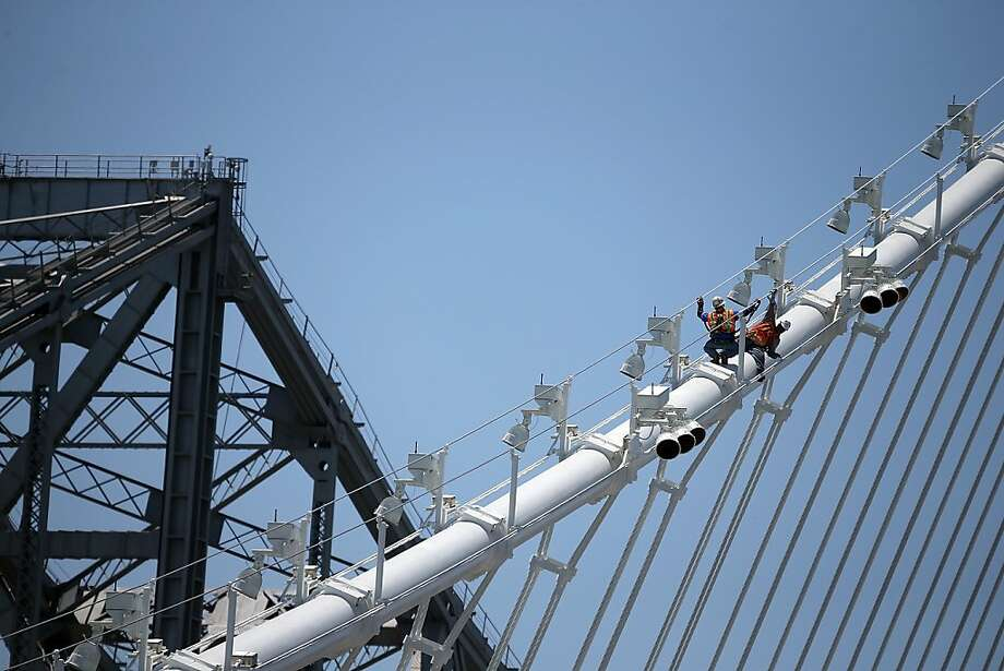 Workers walk on a cable of the newly constructed eastern span of the Bay Bridge, which was scheduled to open on Labor Day weekend before problems arose. Photo: Justin Sullivan, Getty Images