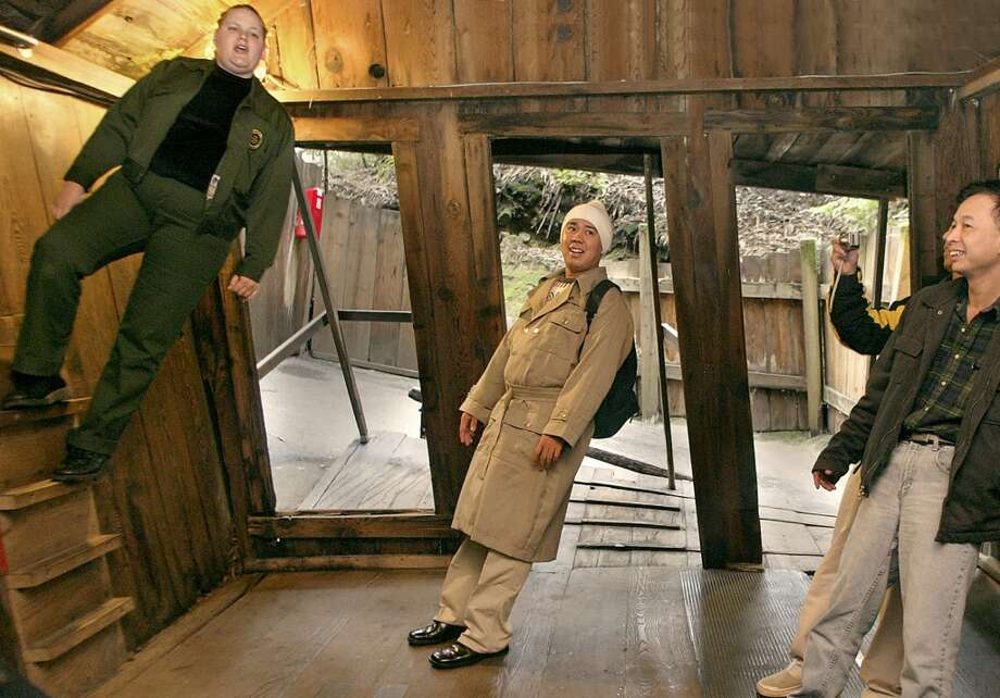 Seeing sideways: Guide Amber Bowyer (left) gives a tour of the Mystery Spot in Santa Cruz, while Gerry Leoncio (middle)  feeling like he's standing straight in this 2003 photo. It's been a roadside attraction since 1940, and responsible for a countless number of bumper stickers.