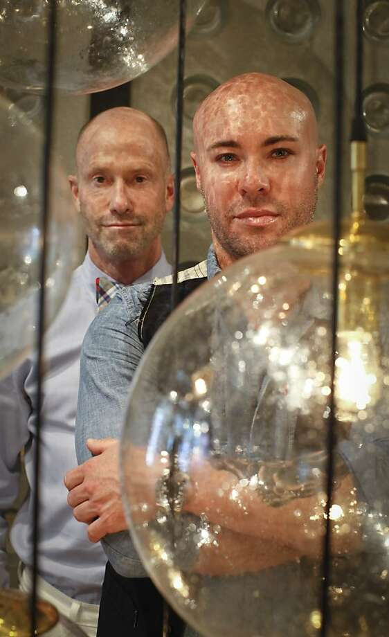 Michael Burg (left) and Darin Geise of Coup d'Etat, with their Celestial Chandelier, and more of their pieces shown on the page. The business is coming out with its first line of original pieces, Coup Studio. Photo: Russell Yip, The Chronicle