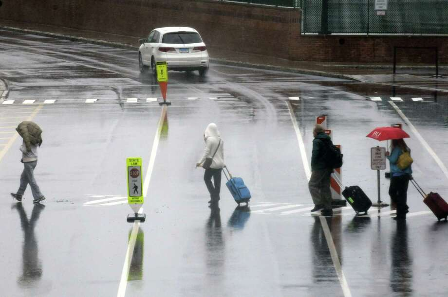 Holiday travelers make their way from the terminal to the parking lot in the rain at Albany International Airport on Friday May 24, 2013 in Colonie, N.Y. (Michael P. Farrell/Times Union) Photo: Michael P. Farrell