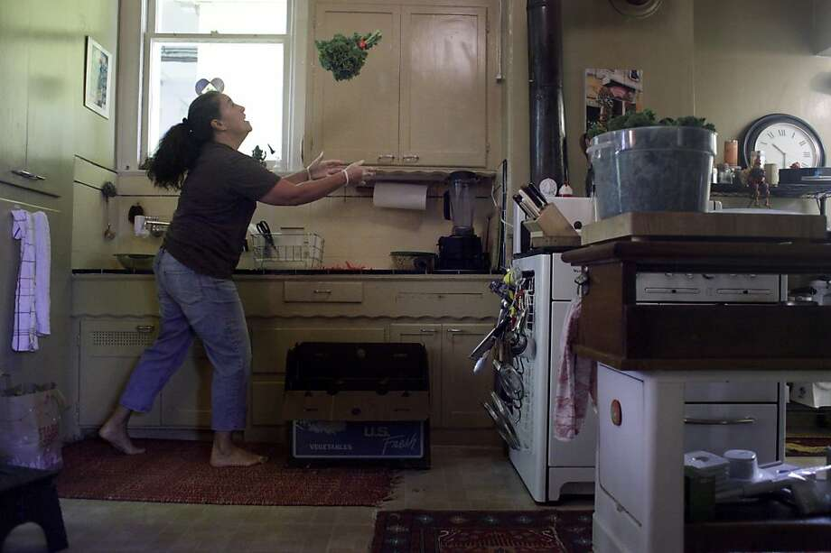A ritual in the making of Kale Mary Full of Taste kale chips, Lisa Laricchiuta tosses handful of kale in her home kitchen in San Francisco. Photo: Mike Kepka, The Chronicle