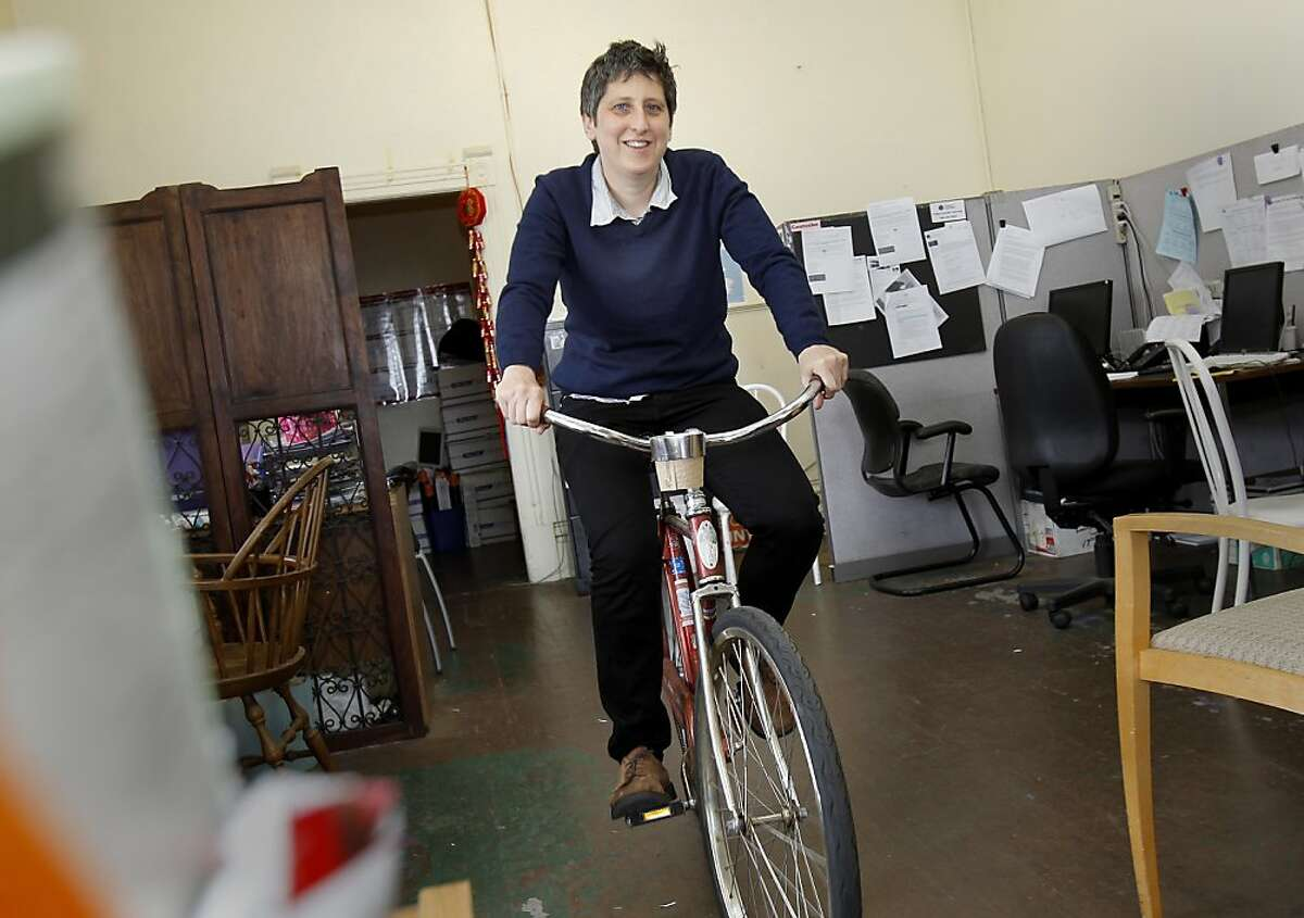 Sara Shortt pedals her bike through her offices on South Van Ness Avenue. Sara Shortt is executive director of the Housing Rights Committee of San Francisco, Calif. She rides her bike to City Hall for meetings Thursday April 25, 2013.