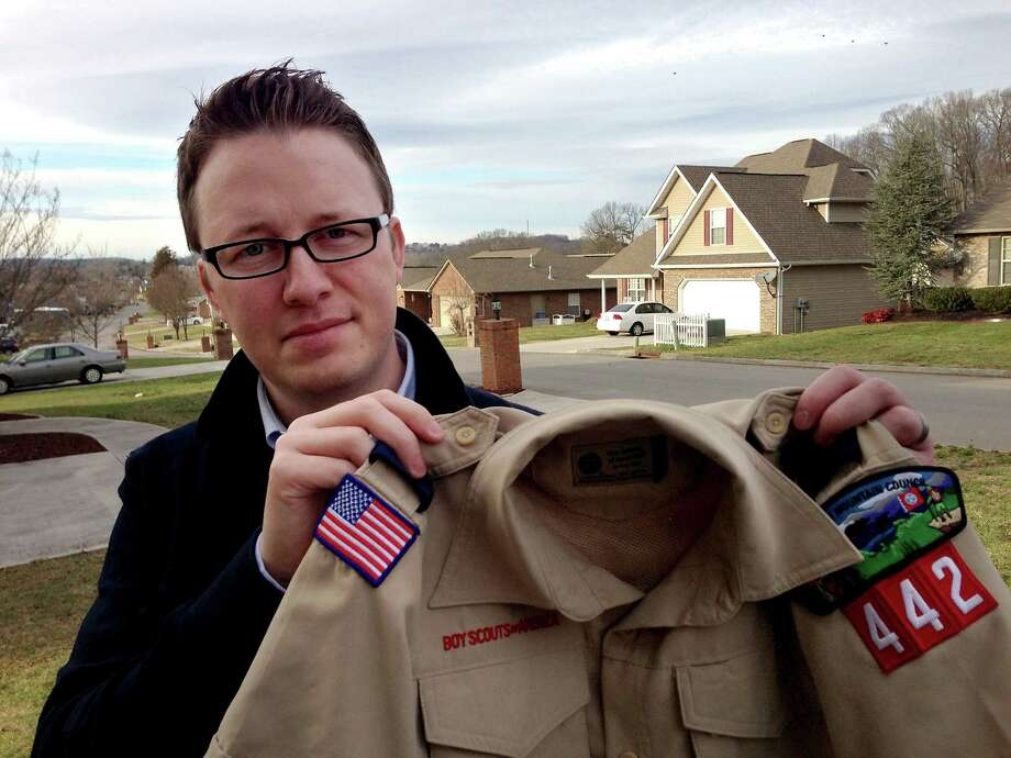 """FILE - In this Monday, Feb. 4, 2013 photo provided by the family, Wes Comer holds the Boy Scout uniform of his son, Isaiah, outside their home in Knoxville, Tenn. Comer, whose family attends an Apostolic Pentecostal church which considers homosexuality sinful, had been wrestling with whether to pull his eldest son out of the Scouts if the no-gays policy was abandoned. """"To be honest, I'm torn at this point,"""" Comer said in an e-mail Friday, May 24, 2013. """"I'm not sure exactly what our decision will be."""" """"If I place this situation in the context of my religious beliefs, I'm forced to ask myself, 'Would I turn a homosexual child away from Sunday School? From a church function? Would I forbid my children to be friends with a gay child?' I can't imagine a situation where I would answer 'yes' to any of those questions. So how can I in this one?"""" he wrote. (AP Photo/Brooke Comer) Photo: Brooke Comer, HONS / Brooke Comer"""