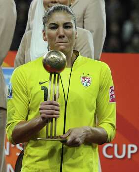 """USA's goalkeeper Hope Solo holds her """"Golden Ball"""" award after the FIFA Women's Football World Cup final match Japan vs USA on July 17, 2011, in Frankfurt am Main, western Germany. Japan won 3-1 in a penalty shoot-out after the final had finished 2-2 following extra-time. Photo: PATRIK STOLLARZ, AFP/Getty Images / 2011 AFP"""