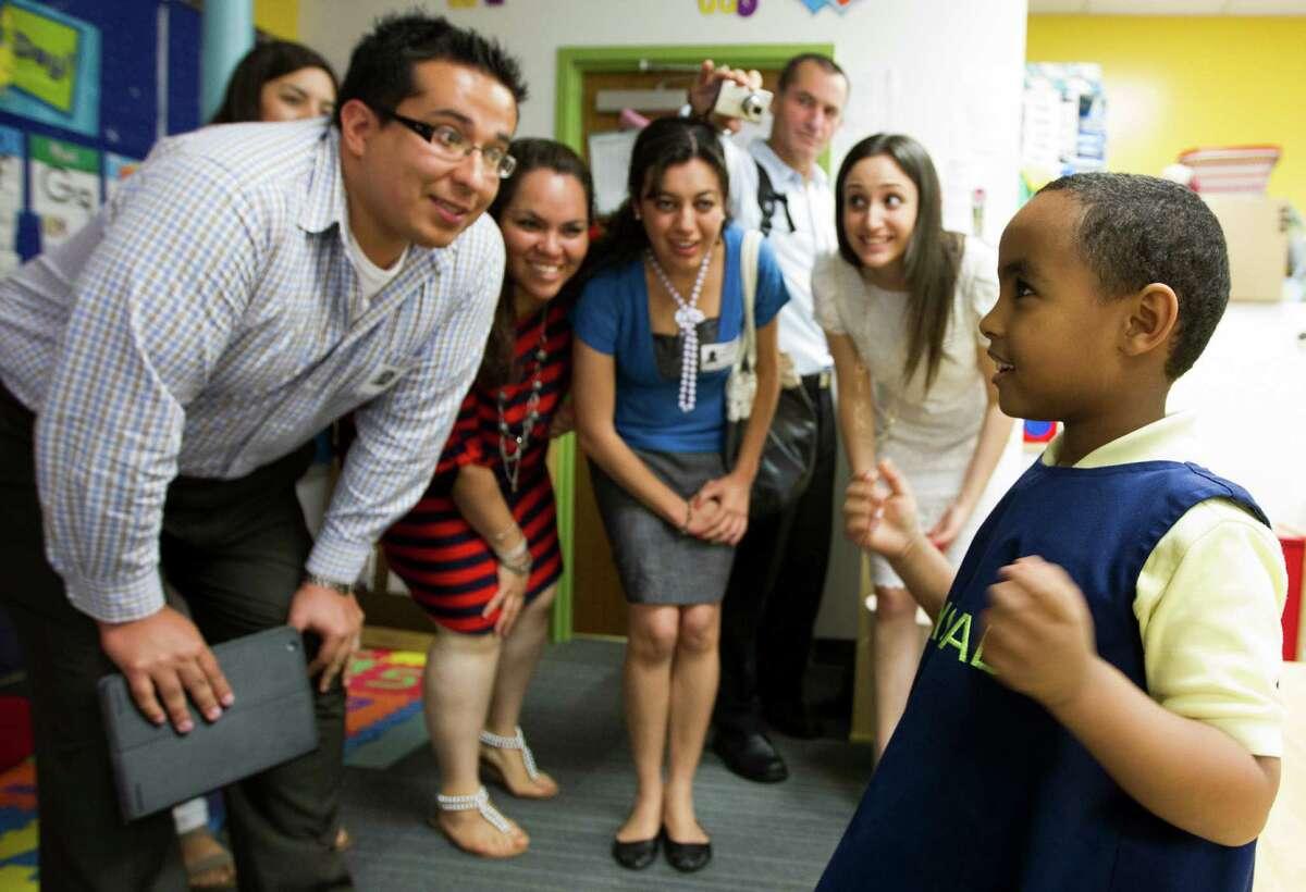 Eyoab Ashagari greets, from left to right, Jose Gerardo Borrego Uma, Karla Mitchell, Maria Avila, Itai Karin, and Yael Karakowsky to his pre-kindergarten class at KIPP Sharp preparatory school this week.