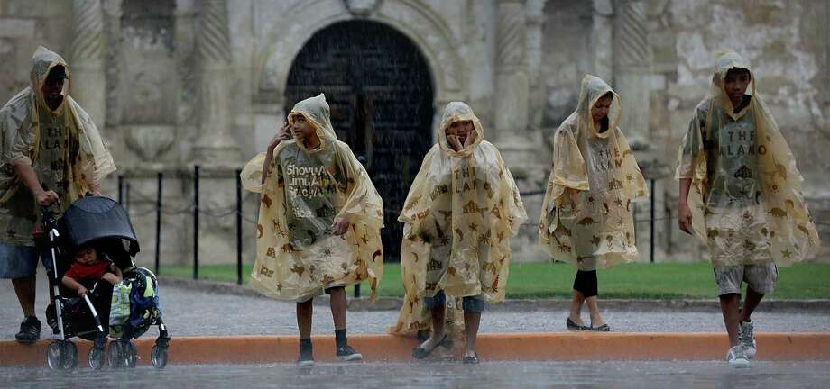 Visitors to the Alamo try to stay dry under rain ponchos from the Alamo as they deal with a downpour. A storm system dropped 2.33 inches of rain at International Airport during the day Friday. Photo: Bob Owen / San Antonio Express-News