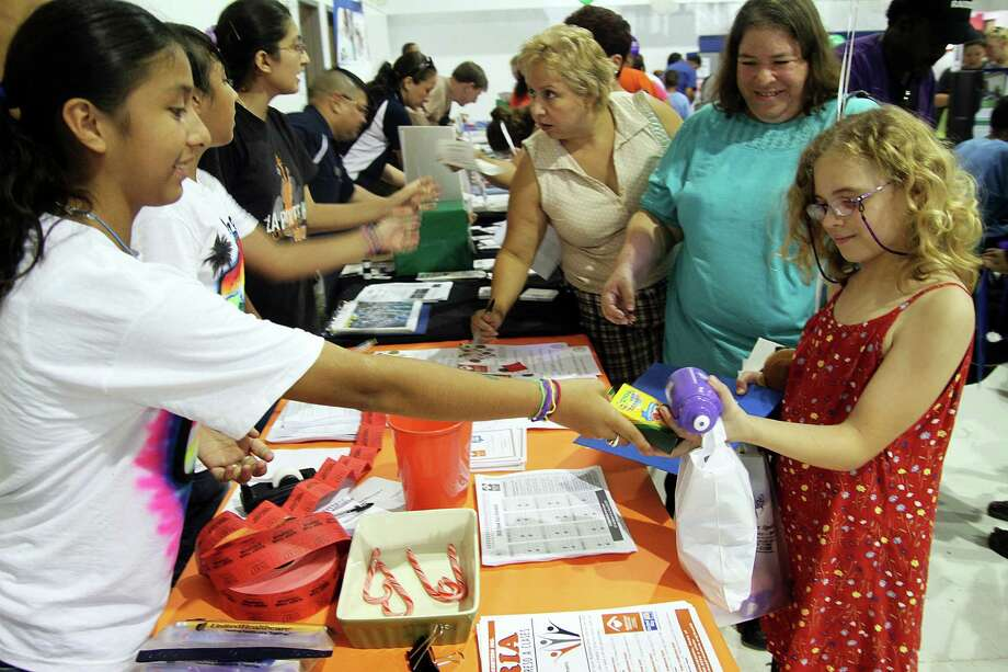 Lesle Gutierrez, left, helped give free school supplies to Mikella Lopez during a 2010 Neighborhood Centers community health fair in La Porte. Policy institutions have begun to study the organizational structure and philosophy of the organization. Photo: Pin Lim, Freelance / Freelance
