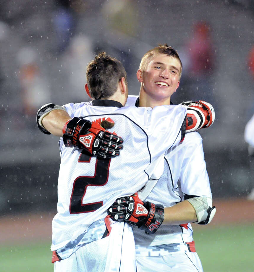 At left, New Canaan's Pete Johnson (# 2) hugs teammate, Thomas Costigan, at the conclusion of the FCIAC boys high school lacrosse championship match in which New Canaan High School defeated Greenwich High School, 8-5, to win the title at Brien McMahon High School in Norwalk, Friday night, May 24, 2013. Photo: Bob Luckey / Greenwich Time