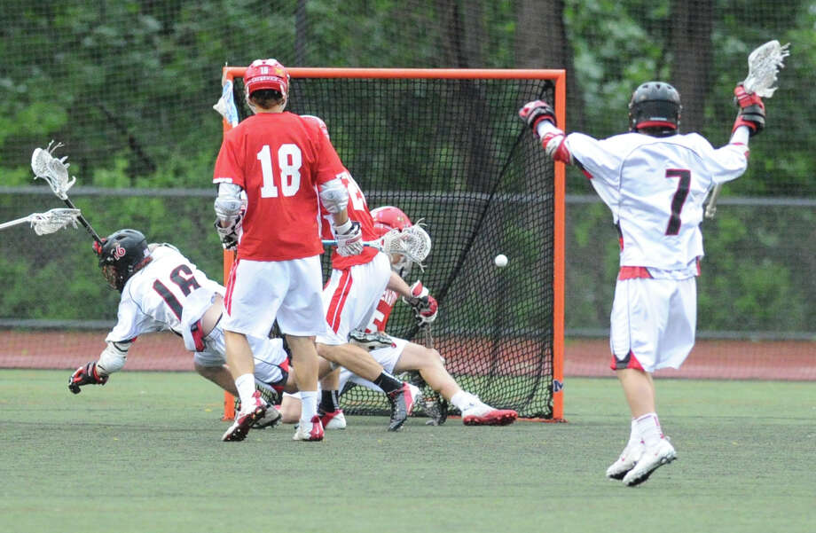 While falling to the turf, Henry Stanton (# 16) of New Canaan High School, left, scores a goal as teammate Cole Turpin (# 7) , right, looks on during the FCIAC boys high school lacrosse championship match between Greenwich High School and New Canaan High School at Brien McMahon High School in Norwalk, Friday night, May 24, 2013. At center is Kelley Jay (# 18) of Greenwich. New Canaan took the title defeating Greenwich, 8-5. Photo: Bob Luckey / Greenwich Time