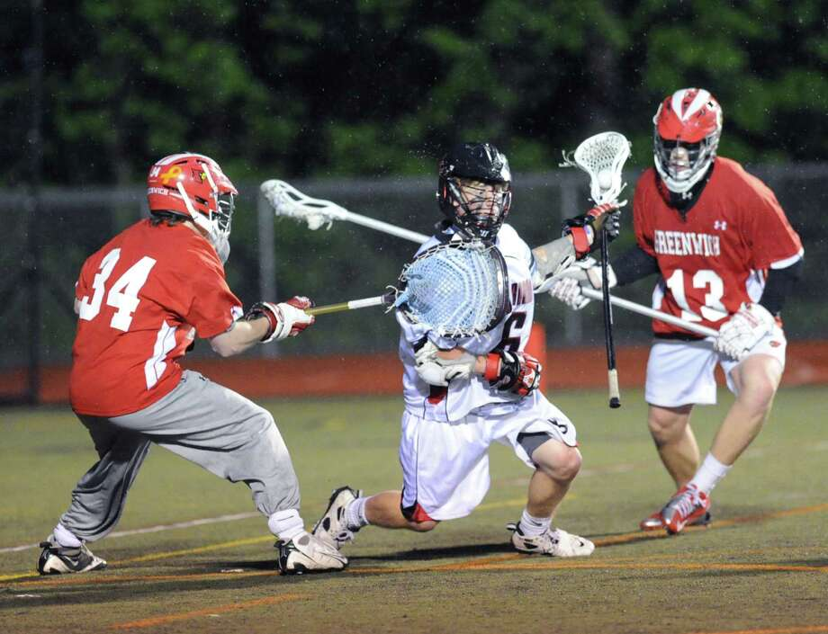 At center, New Canaan's Austin Nader (# 6) runs out the clock while being defended by Thomas Rogan (# 34) of Greenwich, left, and Jack Nail (# 13), also of Greenwich, during the closing minutes of play in the FCIAC boys high school lacrosse championship match between Greenwich High School and New Canaan High School at Brien McMahon High School in Norwalk, Friday night, May 24, 2013. New Canaan took the title defeating Greenwich, 8-5. Photo: Bob Luckey / Greenwich Time