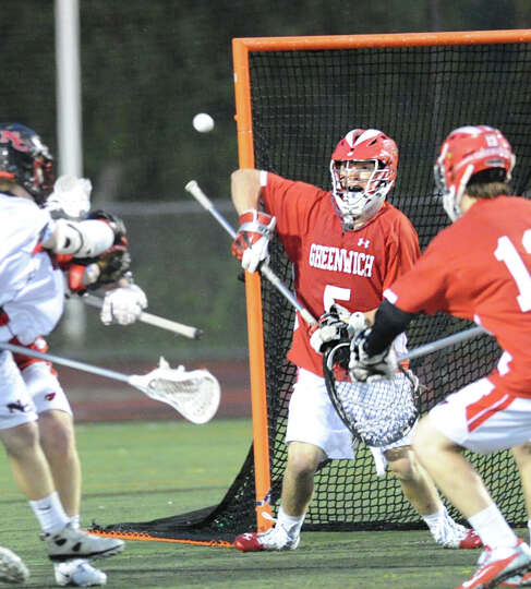 At center, Greenwich High School goalie William Waesche makes a stop during the FCIAC boys high scho