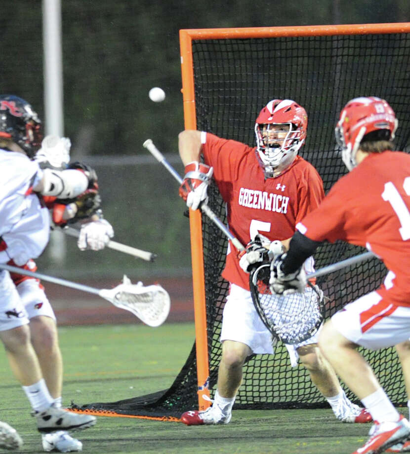 At center, Greenwich High School goalie William Waesche makes a stop during the FCIAC boys high school lacrosse championship match between Greenwich High School and New Canaan High School at Brien McMahon High School in Norwalk, Friday night, May 24, 2013. New Canaan took the title defeating Greenwich, 8-5. Photo: Bob Luckey / Greenwich Time