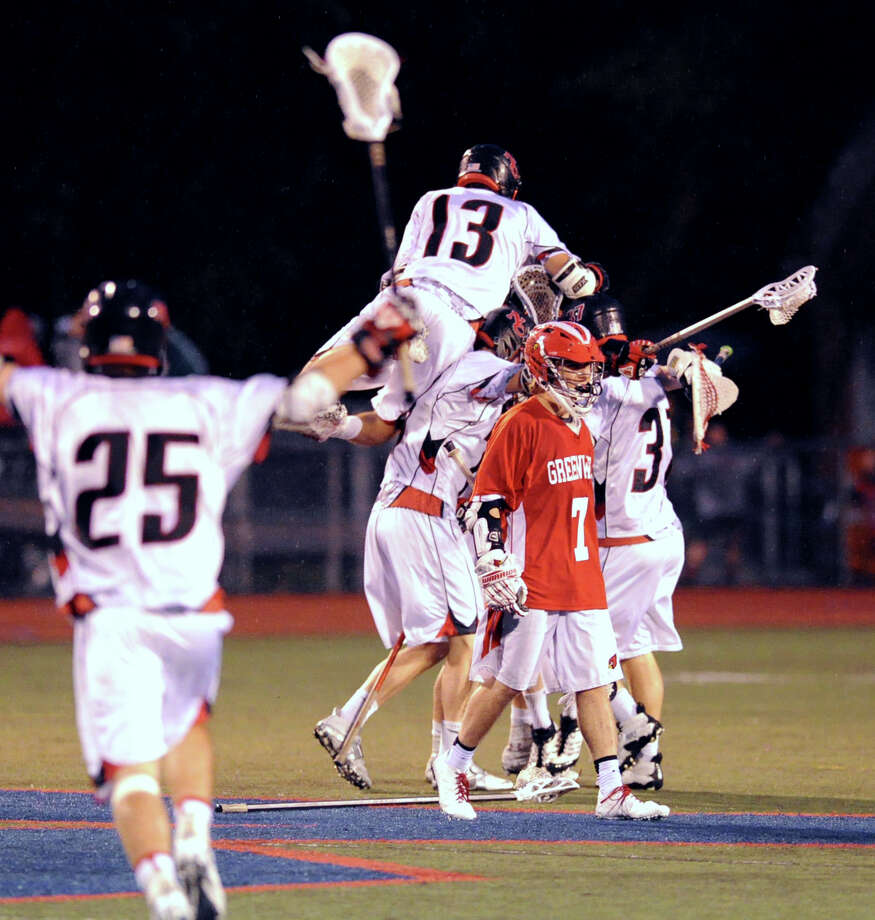 Seth Neeleman (# 13) of New Canaan jumps atop the celebration pile as James Paradise (# 7) of Greenwich walks off the field at the conclusion of the FCIAC boys high school lacrosse championship match between Greenwich High School and New Canaan High School at Brien McMahon High School in Norwalk, Friday night, May 24, 2013. At left about to join the celebration is Duke Repko (# 25) of New Canaan. New Canaan took the title defeating Greenwich, 8-5. Photo: Bob Luckey / Greenwich Time