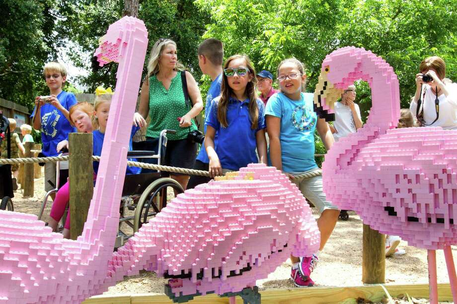 """Jordyn Abalos, 10, left center, and Livia Blackburn, 9, take a look at LEGO flamingos as they explore the new """"LEGO Safari"""" during a preview at the Houston Zoo Friday, May 24, 2013, in Houston. More than two dozen LEGO brick animal sculptures, representing 10 species including flamingos, a tiger, zebra and fish are on display opening May 25 through Labor Day. Photo: Brett Coomer, Houston Chronicle / © 2013 Houston Chronicle"""
