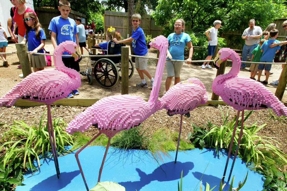 Young visitors walk past a group of LEGO flamingos. Photo: Brett Coomer, Houston Chronicle / © 2013 Houston Chronicle