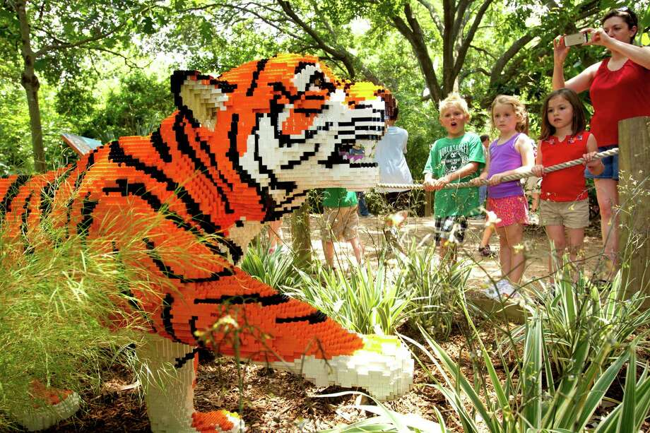Young visitors look at a LEGO tiger they explore the new Animals Assembled exhibit during a preview at the Houston Zoo Friday, May 24, 2013, in Houston. More than two dozen LEGO brick animal sculptures, representing 10 species including flamingos, a tiger, zebra and fish are on display opening May 25 through Labor Day. Photo: Brett Coomer, Houston Chronicle / © 2013 Houston Chronicle