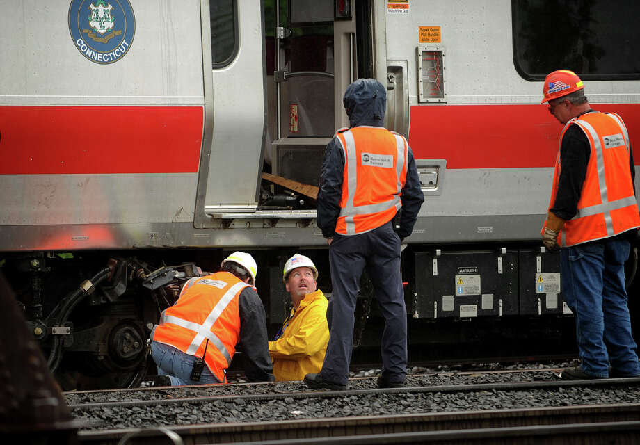 May 2013: Metro North workers prepare train cars to be pulled from the scene of Friday's derailment in Bridgeport. Conn. on Sunday, May 19, 2013. Federal investigators have highlighted two pieces of rail they say were found broken at a joint bar at the accident scene in the area of the crash which injured 76 people. Photo: Brian A. Pounds / Connecticut Post